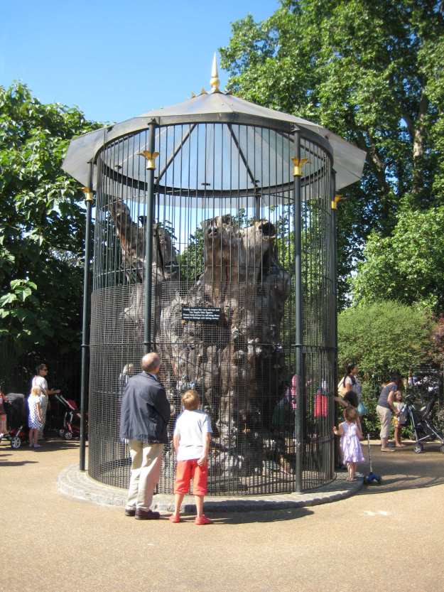 Hyde Park: ancient dead tree with Royal Parks' jokes. Queue for Princess Diana Memorial Playground snaking behind.